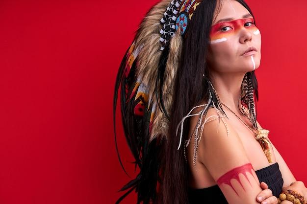 Donna indigena sicura nell'usura sciamanica isolata sopra la parete rossa, femmina indiana mistica in studio. persone individualità, diversità, concetto di etnia