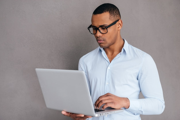 Esperto it sicuro. fiducioso giovane africano che lavora al computer portatile