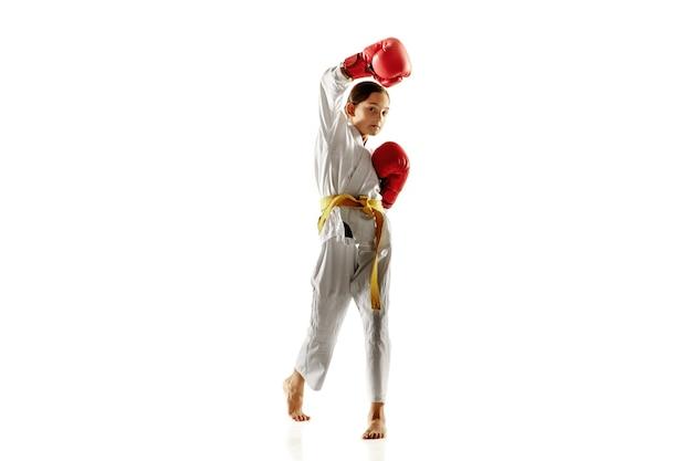Junior fiducioso in kimono che pratica combattimento corpo a corpo, arti marziali. giovane combattente femminile con l'addestramento della cintura gialla sulla parete bianca. concetto di stile di vita sano, sport, azione.