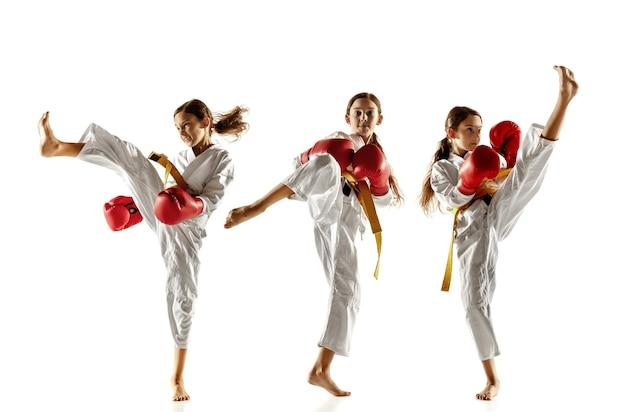 Fiducioso junior in kimono che pratica arti marziali da combattimento corpo a corpo