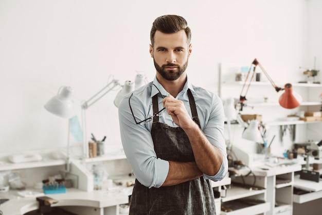 Capo fiducioso. ritratto di gioielliere maschio fiducioso che indossa un grembiule e tiene gli occhiali mentre si trova in uno studio di creazione di gioielli.