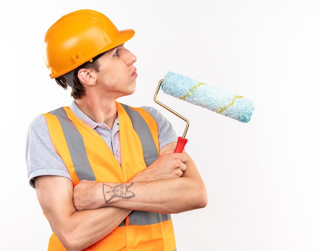 Fiducioso dall'aspetto laterale giovane costruttore uomo in uniforme che si incrocia con le mani che tengono la spazzola a rullo