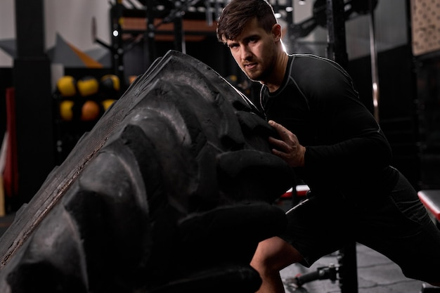 Fiducioso atleta maschio che fa esercizio di ribaltamento dei pneumatici al chiuso nella moderna palestra. cross fit e allenamento. atleta forte e bello in abbigliamento sportivo. sport, stile di vita sano