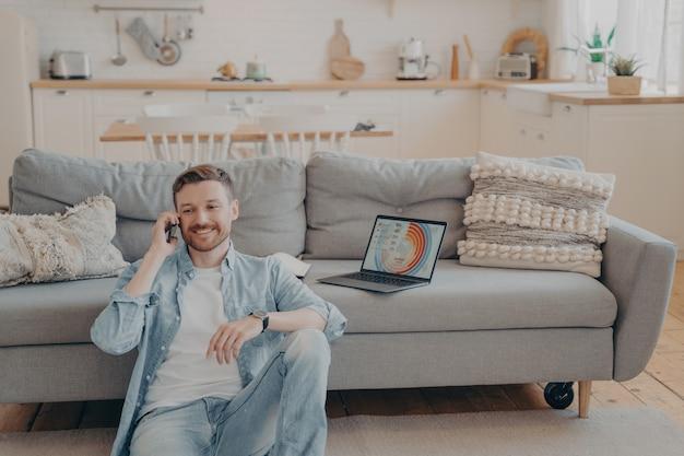 Fiducioso lavoratore freelance maschio che chiama il suo datore di lavoro per comunicargli buone notizie sul progetto, rendendo soddisfatto un altro cliente, laptop con infografica, seduto sul pavimento mentre si riposa contro il divano