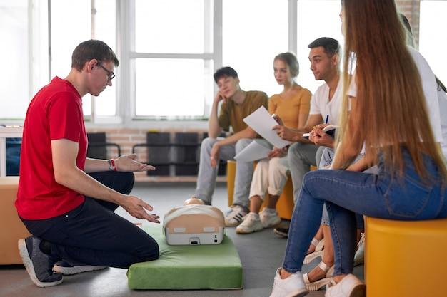 Fiducioso istruttore maschio mostra e parla della prima rcp di emergenza