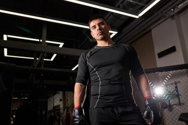 Pugile sicuro dell'uomo in guanti che stanno dopo la lotta. giovane pugile durante l'allenamento. concetto di forza e motivazione. ritratto di uomo che guarda la telecamera