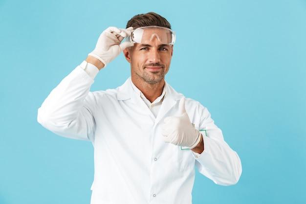 Fiducioso uomo medico indossando uniformi in piedi isolato sopra la parete blu, dando i pollici in su