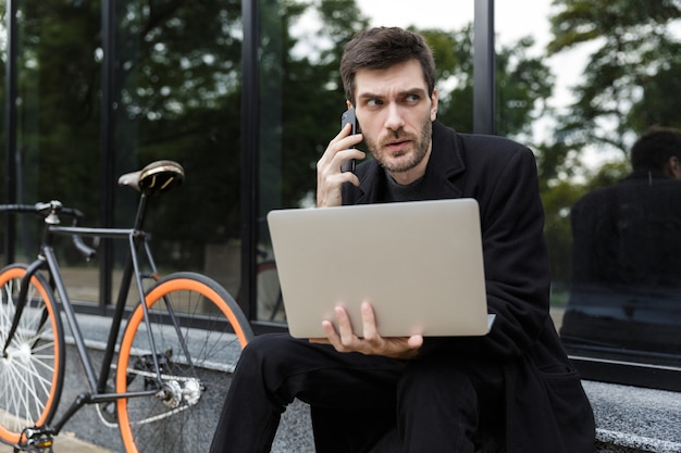 Fiducioso uomo vestito con un cappotto seduto per strada, utilizzando il computer portatile, parlando al telefono cellulare