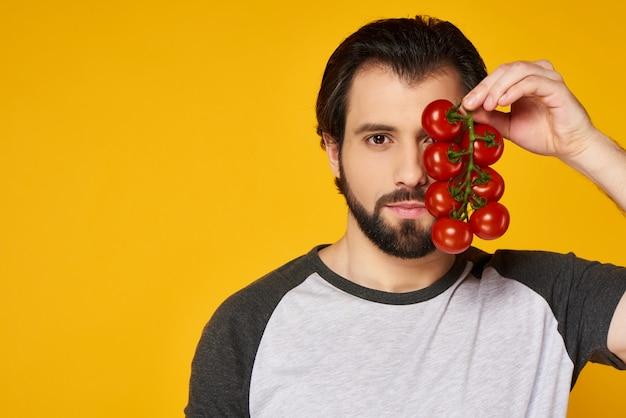 L'uomo sicuro tiene il mazzo di pomodori davanti alla faccia.