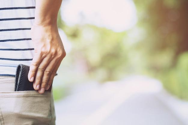 Uomo fiducioso in posa in sicurezza mantenendo il portafoglio nella tasca posteriore dei pantaloni della tasca posteriore. risparmio di denaro.