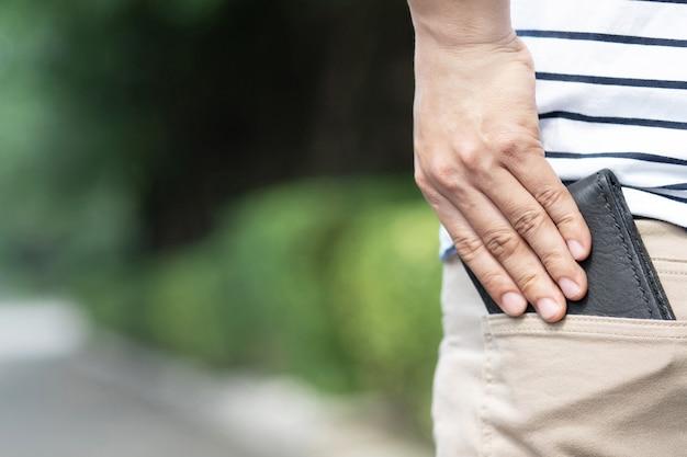 Uomo fiducioso in posa in sicurezza mantenendo il portafoglio nella tasca posteriore dei pantaloni della tasca posteriore.