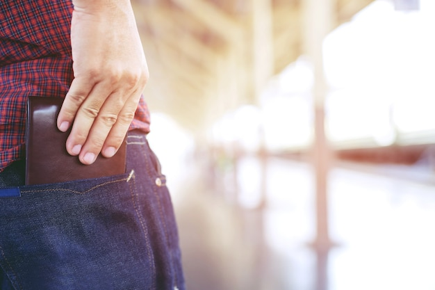 Uomo fiducioso in posa in sicurezza mantenendo il portafoglio nella tasca posteriore dei pantaloni della tasca posteriore