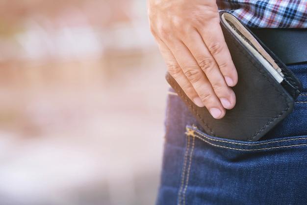 Uomo fiducioso in posa per salvare mantenendo il portafoglio nella tasca posteriore dei pantaloni della tasca posteriore dei jeans.
