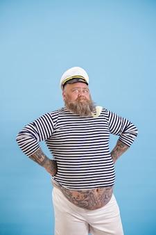 L'uomo sicuro con sovrappeso in abito da marinaio tiene le mani sulla vita su sfondo azzurro
