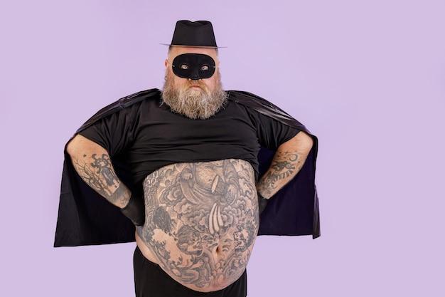 L'uomo sicuro con sovrappeso in tuta zorro tiene le mani sulla vita su sfondo viola