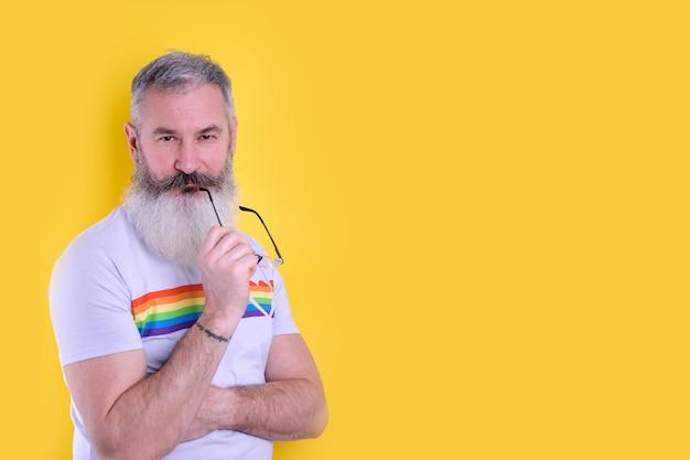 Fiducioso maturo uomo barbuto vestito con t-shirt simboli lgbtq guardando la telecamera, ritratto in studio di uomo omosessuale, sfondo giallo