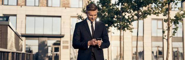 Uomo d'affari maturo sicuro che guarda il telefono cellulare mentre cammina vicino all'edificio per uffici all'aperto