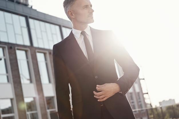 Uomo d'affari maturo sicuro che cammina vicino all'edificio per uffici all'aperto