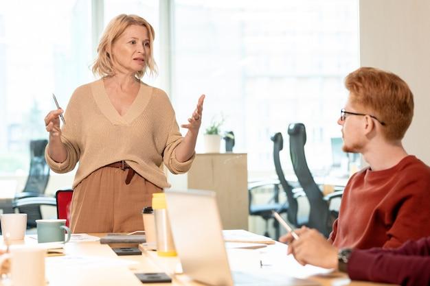 Fiduciosa donna di affari matura che spiega qualcosa a giovani subordinati o colleghi durante la formazione aziendale o la riunione