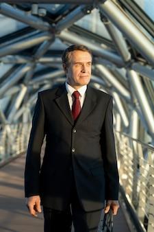 Delegato o uomo d'affari maturo fiducioso con borsa in pelle nera in piedi davanti alla telecamera all'interno del centro business contemporaneo