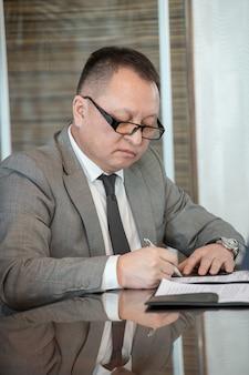 Delegato maturo fiducioso in abito elegante che firma un contratto di partnership commerciale con un partner straniero mentre è seduto al tavolo nella sala riunioni