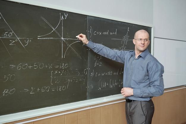 Fiducioso professore maturo in piedi davanti alla lavagna nell'aula magna, indicando il grafico e spiegandolo mentre guarda il pubblico
