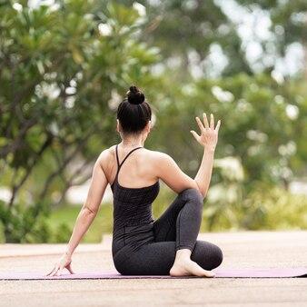 Una donna asiatica di mezza età sicura in abbigliamento sportivo che fa esercizio di yoga sul tappetino da yoga all'aperto nel cortile di casa al mattino. giovane donna che fa esercizio di yoga all'aperto nel parco pubblico naturale