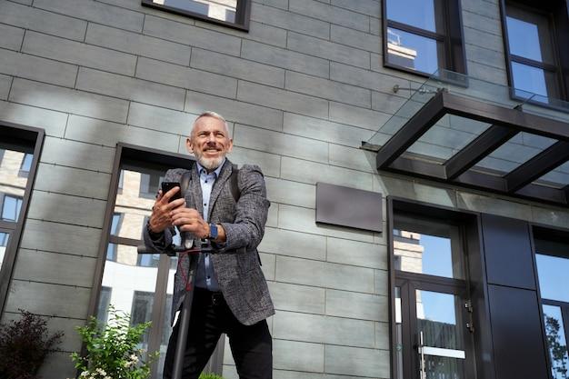 Fiducioso uomo d'affari di mezza età che sorride tenendo in mano il suo telefono cellulare mentre sta in piedi con l'elettrico