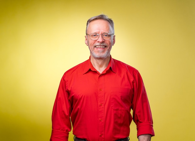 Fiducioso uomo di mezza età in camicia rossa con braccia dritte su sfondo giallo