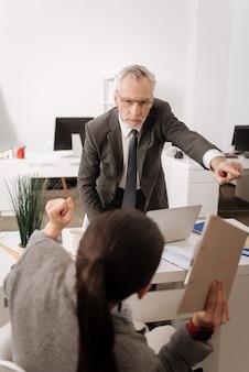 Impiegato fiducioso in piedi vicino al suo posto di lavoro alzando il braccio sinistro mentre guarda il suo manager