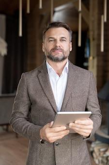 Fiducioso proprietario del ristorante con tavoletta digitale in piedi davanti alla telecamera mentre guarda i dati sul proprio sito web