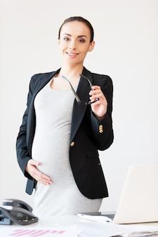 Donna di affari incinta sicura. bella donna d'affari incinta che tiene gli occhiali e sorride mentre si trova vicino al suo posto di lavoro in ufficio