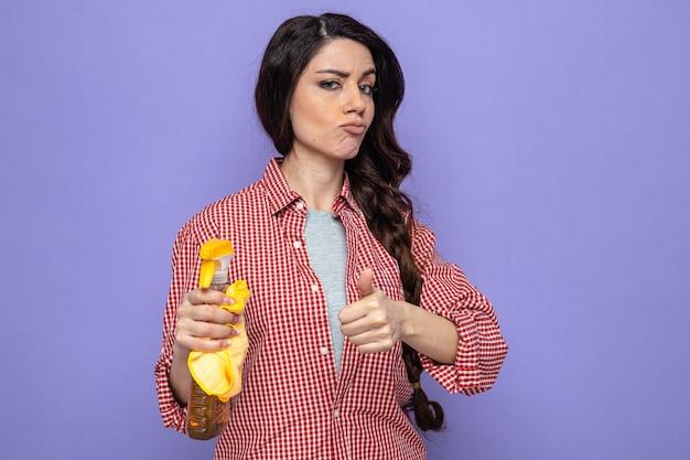 Donna pulita abbastanza caucasica sicura che tiene in mano panni per la pulizia con detergente spray e pollice in alto