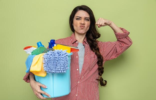 Fiduciosa donna delle pulizie piuttosto caucasica che tiene in mano le attrezzature per la pulizia e tende i bicipiti