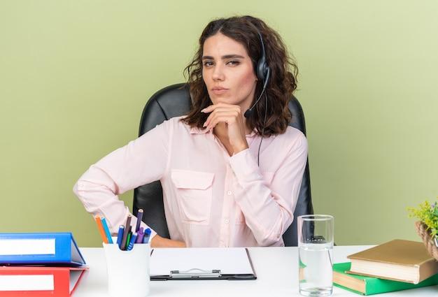 Operatore di call center femminile piuttosto caucasico fiducioso sulle cuffie seduto alla scrivania con strumenti da ufficio che mettono la mano sul mento