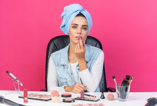 Donna abbastanza caucasica sicura con i capelli avvolti in un asciugamano seduto al tavolo con strumenti per il trucco che applicano rossetto