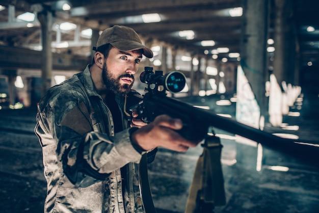 Professionista fiducioso sta mantenendo il silenzio. sta guardando bene e tiene il suo fucile con entrambe le mani. l'uomo è pronto a sparare.