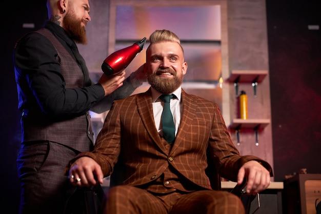Barbiere maschio professionista sicuro con un asciugacapelli che asciuga i capelli di un giovane uomo caucasico bello