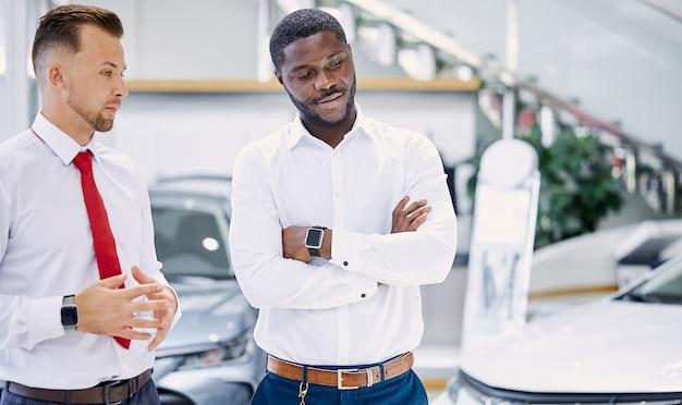Il venditore professionista fiducioso parla delle caratteristiche dell'auto