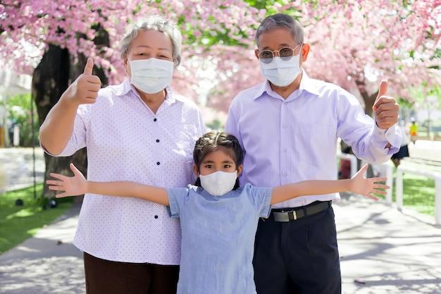 Fiducioso e proteggere il parco all'aperto con la famiglia asiatica.