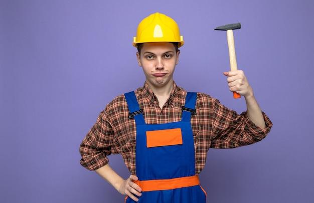 Fiducioso mettendo la mano sull'anca giovane costruttore maschio che indossa l'uniforme che tiene martello