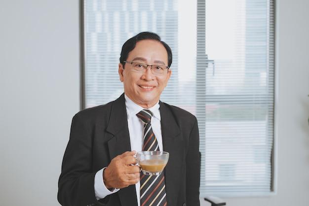 Fiducioso senior business leader asiatico in piedi in ufficio