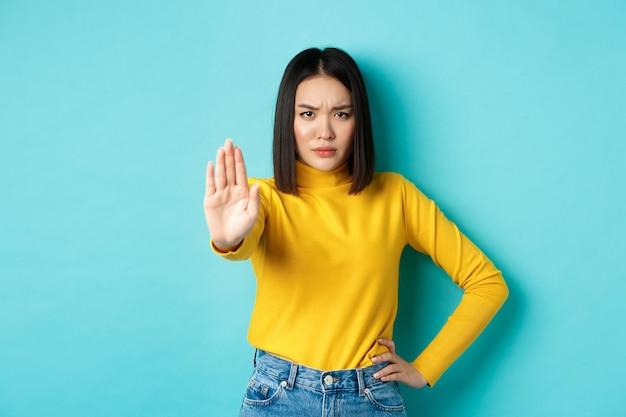 La donna asiatica sicura e seria dice di no, mostrando il gesto di arresto per vietare e avvertire, non essere d'accordo con qualcuno, in piedi sconvolto contro lo sfondo blu.
