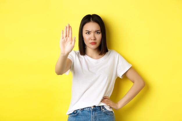 La donna asiatica sicura e seria dice di no, mostrando il gesto di arresto per vietare e avvertire, non essere d'accordo con qualcuno, in piedi sconvolto su sfondo giallo.