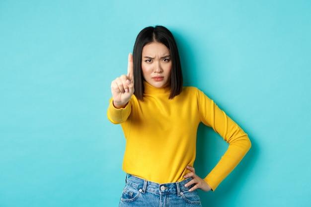 La donna sicura e seria dice di no, mostrando il dito esteso per fermarsi e proibire qualcosa di brutto, aggrottando la fronte e guardando la telecamera sicura di sé, in piedi su sfondo blu.