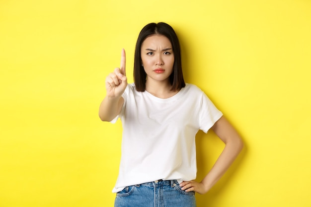 La donna sicura e seria dice di no, mostrando il dito esteso per fermarsi e proibire qualcosa di brutto, aggrottando la fronte e guardando la telecamera sicura di sé, in piedi su sfondo giallo.