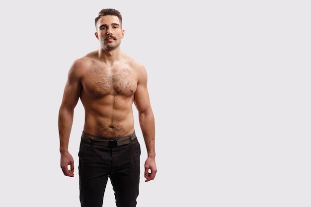 Fiducioso uomo barbuto sexy, seriamente brutale con il torso nudo, su sfondo blu. spazio per il testo. hipster maturo con la barba.