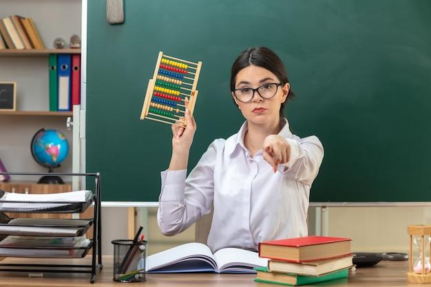 Fiducioso che ti mostra gesto giovane insegnante femminile che indossa occhiali con in mano l'abaco seduto al tavolo con gli strumenti della scuola in classe