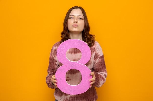 Fiducioso showinh bacio gesto bella ragazza il giorno della donna felice tenendo il numero otto