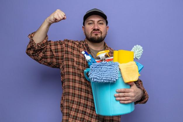 Fiducioso uomo delle pulizie slavo che tiene in mano le attrezzature per la pulizia e tiene il pugno alzato